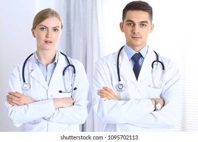 Doctors standing straight with arms crossed in hospital. Physicians ready to help. Concept of healthcare, teamwork and perfect service in medicine