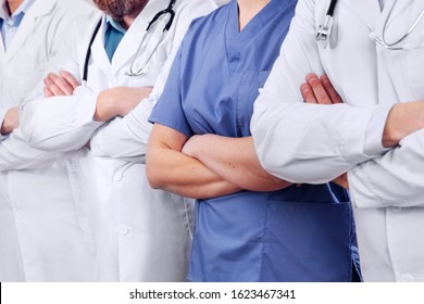 Doctors and surgeons in healthcare team with arms crossed in a row in hospital