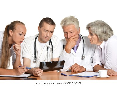 Doctors at the table on white background exemining xray