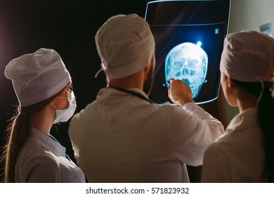 Doctors watching x-ray of patient.