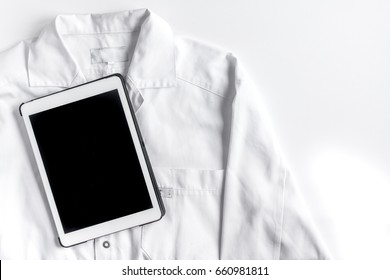 doctor's work with overall and tablet on hospital desk background top view mock up