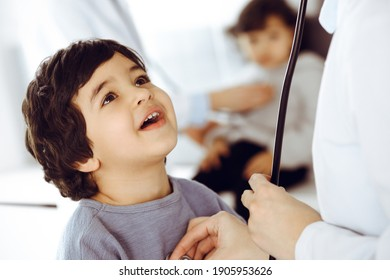 Doctor-woman examining a child patient by stethoscope. Cute arab boy and his brother at physician appointment. Medicine concept