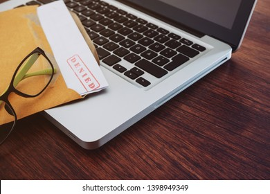 Document with denied stamp and laptop put on the wooden table.
