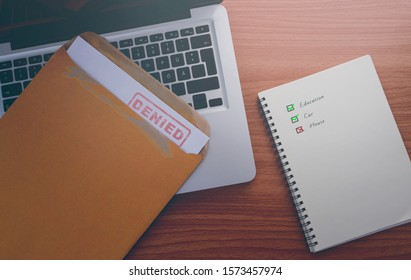 Document with denied stamp put on the laptop on wooden table.