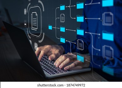 Document Management System (DMS) being setup by IT consultant working on laptop computer in office. Software for archiving, searching and managing corporate files and information. Business processes - Shutterstock ID 1874749972