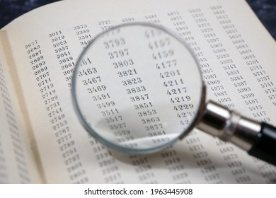 document with many numbers and magnifier, data encrypt. Cipher encryption code or data, closeup