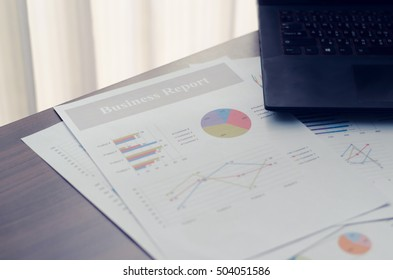 Document paper chart and laptop on desk. Reports work data analysis in office. Curtain background