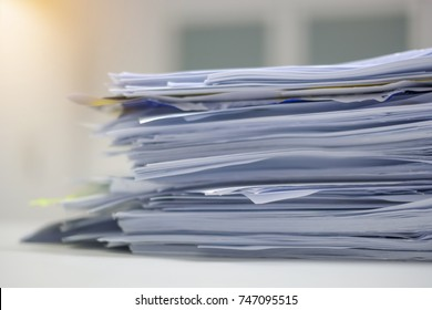 Document pile on office desk, Stack of business paper on the table with blurred of meeting room interior background. job interview and busy business concepts.