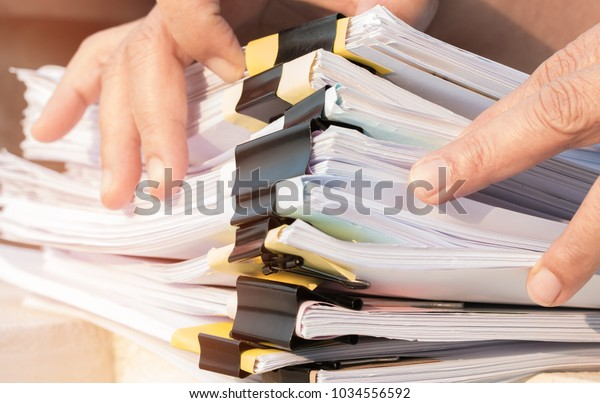 Document Report and business busy Concept: Asian Businessman hands working in many documents Stacks of folders in office for Annual Report files, Piles of unfinish sheet folder close annual budget.