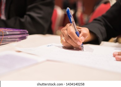 Document Report and Education Concept: Teacher woman hands holding pen for checking signing and note on white documents reports papers of paper files in meeting seminar room background.