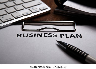Document with title business plan and office supplies close up