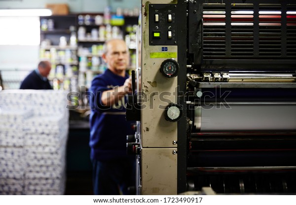 Documentary photography of a commercial printer: a Heidelberg printer with male employees and the interior of a print workshop
