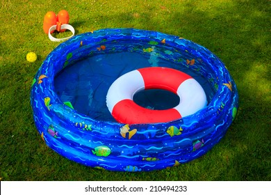 Documentary Picture of a wading pool and swim gear during a Beautiful summer day.