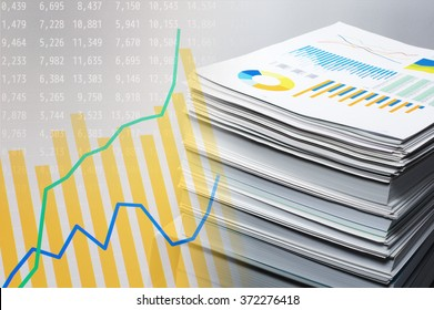 Documentation and data analysis. Business concept. Pile of documents on gray background. Graph and data on monitor display.