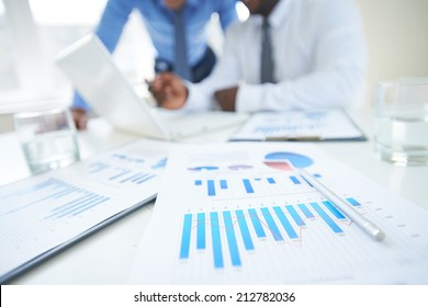 Documents with chart and graph and pen on background of two employees working