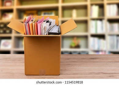 The documents and files are placed in a brown box on the table.