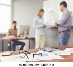 Documents and glasses on the table, in the background beautiful business people are working in office