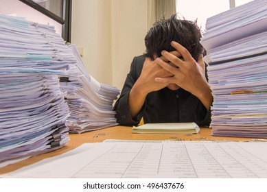documents on desk stack up high waiting to be managed.