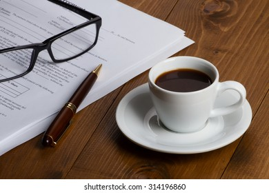 Documents with pen, glasses and coffee cup over wooden table
