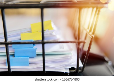Documents placed in the office in the document basket, using clips to separate the types of important content.