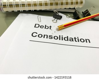 Documents with title debt consolidation on an office table. Debt consolidation is something that people come to consider when and if they find themselves dealing with the burden of debt.