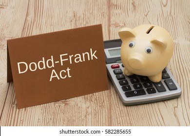 The Dodd-Frank Act, A golden piggy bank, card and calculator on a wood desk with text Dodd-Frank Act