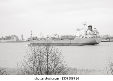 Doel, Antwerp, Belgium – February 2019: Large cargo ship leaving the Antwerp harbor heading for the open sea in black and white
