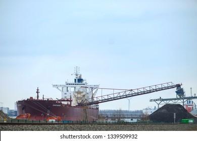 Doel, Antwerp, Belgium – February 2019: Large cargo ship unloading in the dock of the Antwerp harbor