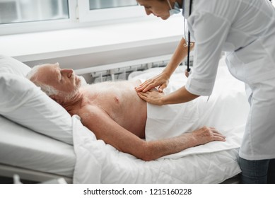 Does it hurt. Side view portrait of shirtless old man lying in bed while physician palpating his abdomen