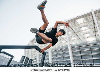 Does parkour. Young man in sportive clothes have workout outdoors at daytime.
