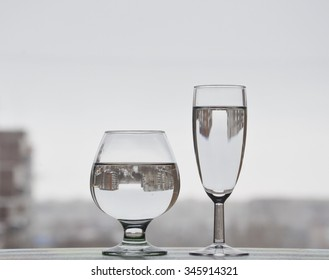 Does size matter? Big and small stemware/glasses of water in which the city is reflected.