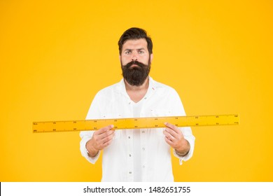 Does size really matter. Man bearded hipster holding ruler. Measure length. Size tall and length. Big size. Measure and control. Geometry theorem. Actual size. School teacher. Small little big large.