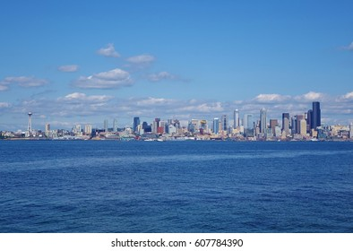 It doesn't always rain in Seattle. Beautiful summer day looking across Elliott Bay from West Seattle at entire skyline of Seattle with a nice blue sky scattered with white puffy clouds. August 2016.