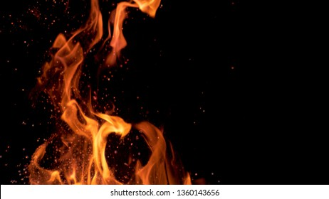 DOF, MACRO: Beautiful bright orange flames flicker in the darkness of the night. Orange campfire blazing and spitting out glowing particles. Cinematic shot of a crackling bonfire in complete dark.