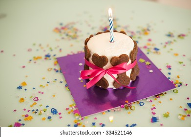 dog birthday cake with bone cookies, ribbon and candle