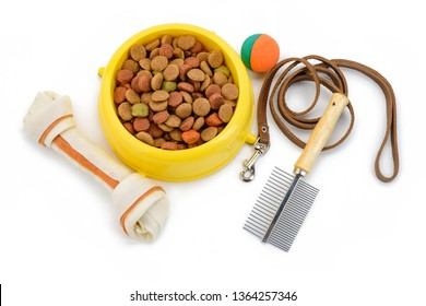 Dog bone, bowl of kibbles, ball toy, leash and brush, top view. Proper nutrition, playtime and care for active pup.
