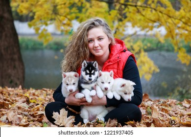 Dog breeder with his pets in an autumn park