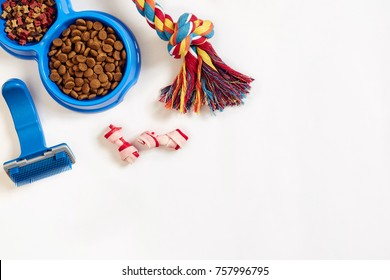 Dog care items, isolated on white background. Dry pet food in bowl, toy and bones. Top view