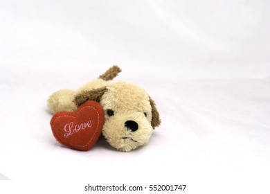 dog doll with red heart on white background