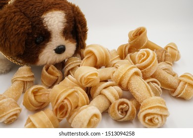 Dog doll toy with pool of knotted bone or rawhide or dog bone on white background, reward and incentive concept