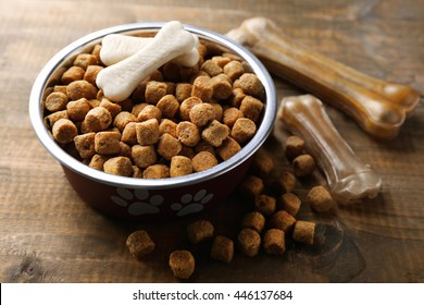 Dog food in metallic bowl on wooden background