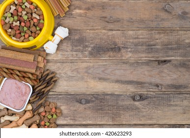 Dog food selection on wooden background with copy space, top view