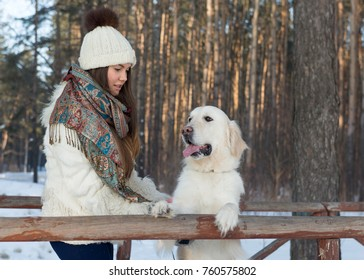 The dog is a Golden Retriever standing on its hind legs. Girl with a Golden Retriever on a background of nature. Girl playing with dog in the nature.
