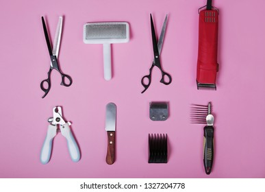 dog grooming tools and accessories set on pink background. pet care and hygienic concept, flat lay. Scissors, coat clipper, brush,  Nail Clipper, thinning scissors. Top view.