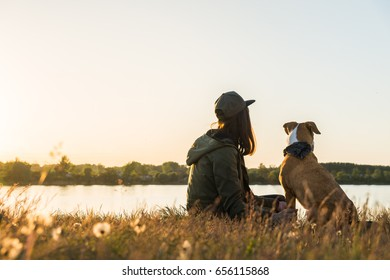 Dog and her owner sit by the lake at sunset. Girl in parka and cap with puppy in bandana on hike sit together and enjoy beautiful view at the river at dawn
