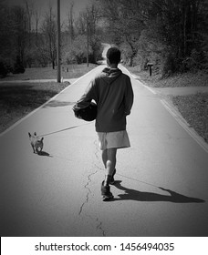 A dog and his boy with his basketball walking down a lonely, deserted street