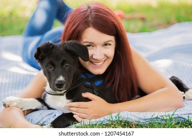 Dog and his owner sitting on green grass in a city park having fun.Puppy and young woman having fun in a park - Concepts of friendship,pets,togetherness.
