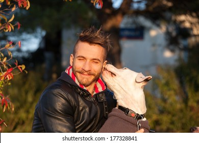 Dog kissing a smiling young man