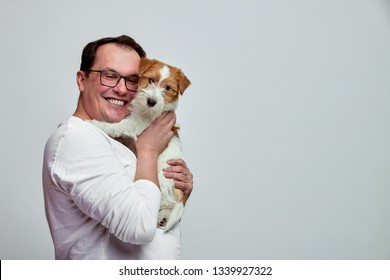 The dog lies on the shoulder of its owner. Jack Russell Terrier in his owner's hands on white background. The concept of people and animals. T