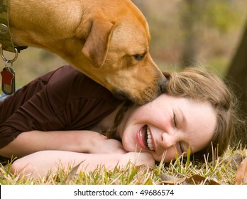 Dog making girl laugh on grass